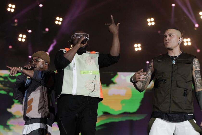 Will.i.am, centro, Taboo, derecha, y apl.de.ap de los Black Eyed Peas durante su presentación