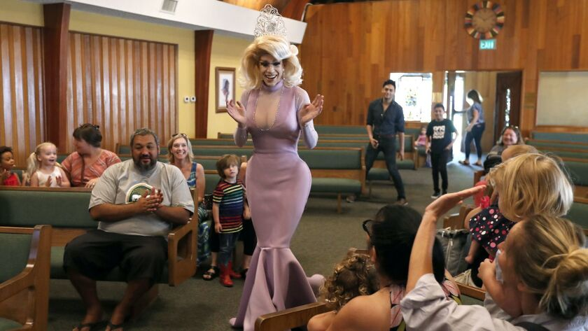 Drag queen Autumn Rose greets children and parents before reading children's books to them at Fairvi