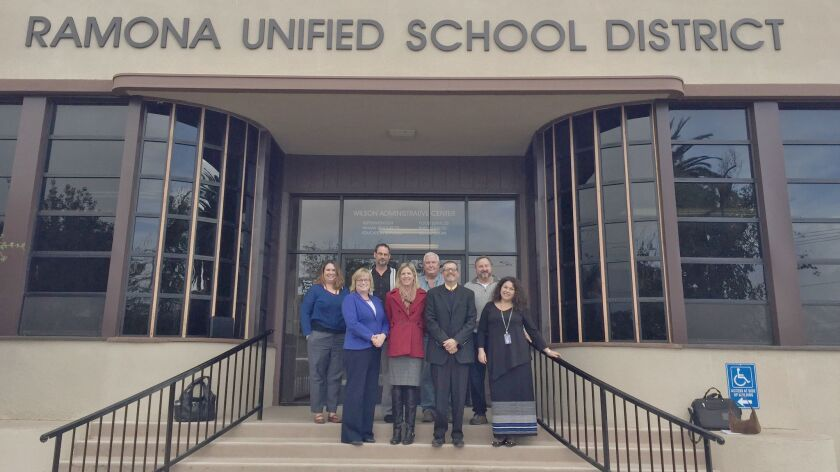 County and district officials stand on the steps of the Ramona Unified School District building after learning that teacher Gloria Quinn (front right) and her Eco-Leaders program is a national award winner.