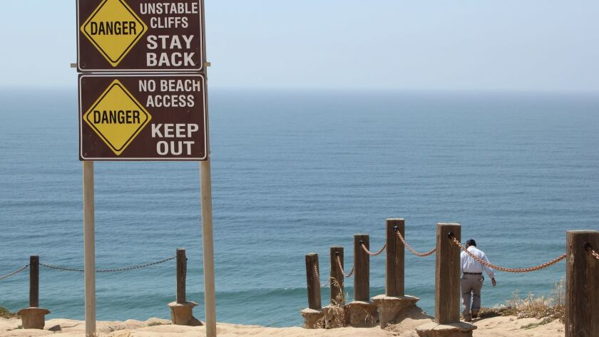 """""""Danger"""" signs don't stop beach-goer from walking down the bluffs at Torrey Pines Gliderport April 2"""