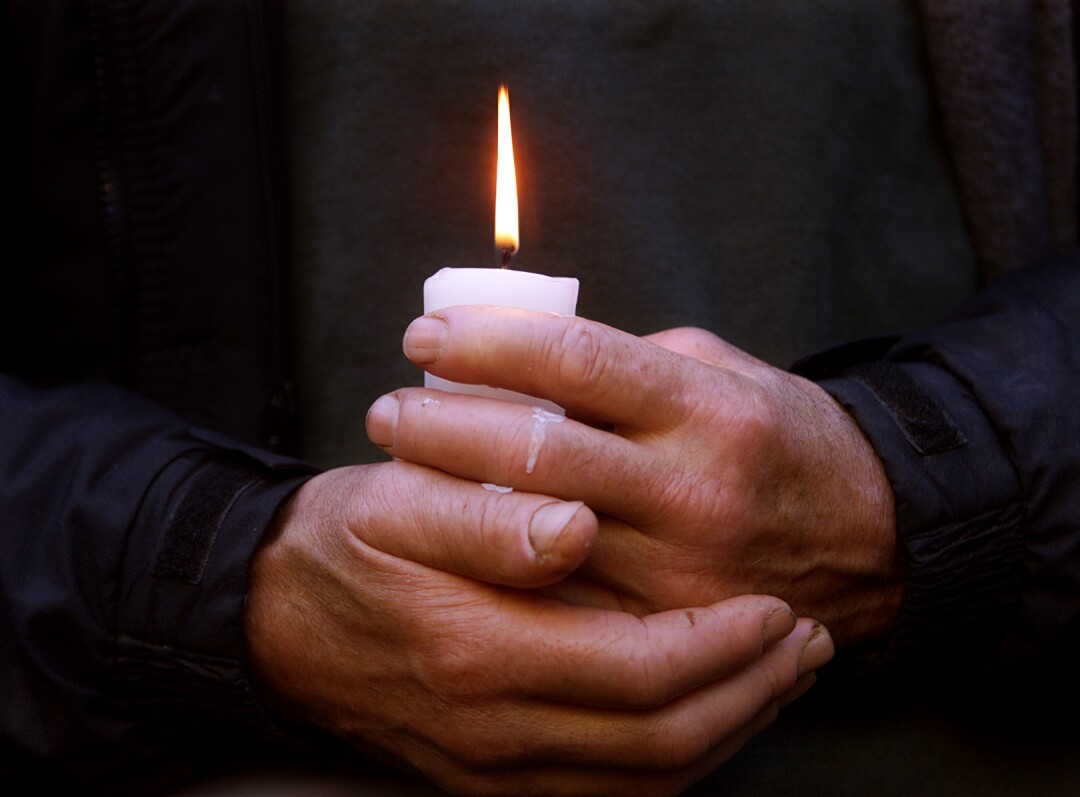 A pair of hands hold a lit candle