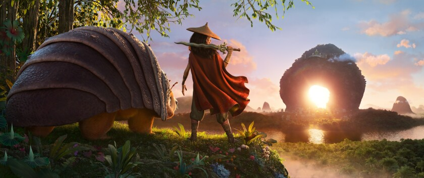 """Animated character Raya, voiced by Kelly Marie Tran, center, appears with Tuk Tuk, voiced by Alan Tudyk, in a scene from """"Raya and the Last Dragon."""" (Disney+ via AP)"""