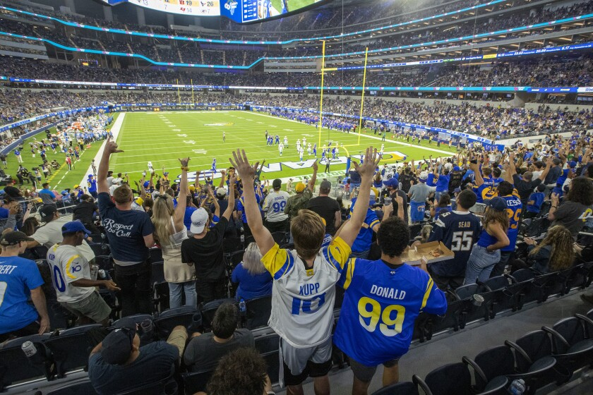 A wide-angle view of fans cheering in a packed football stadium.