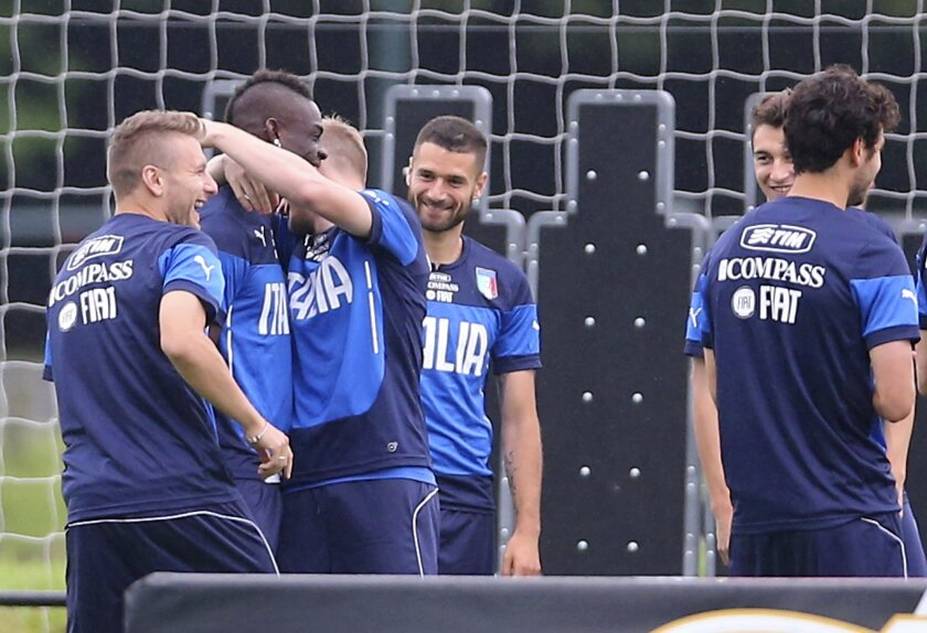 Italy's Ignazio Abate embraces Mario Balotelli during a training session in Mangaratiba, Brazil, Tuesday, June 10, 2014. Balotelli took care of some personal business before the World Cup training session, proposing to his Belgian girlfriend Fanny Neguesha early Tuesday morning. Italy's squad applauded Balotelli and he responded with a wave of his hand and a wide smile. Then teammates Antonio Candreva, center left, Ciro Immobile, left, and Abate went over to offer a congratulatory hug. (AP Photo/Antonio Calanni)
