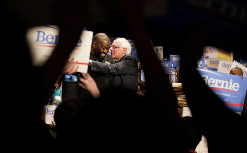 Democratic presidential candidate Sen. Bernie Sanders, I-Vt., right, embraces rapper Killer Mike after speaking onstage at a campaign event at the Fox Theatre Monday, Nov. 23, 2015, in Atlanta. (AP Photo/David Goldman)