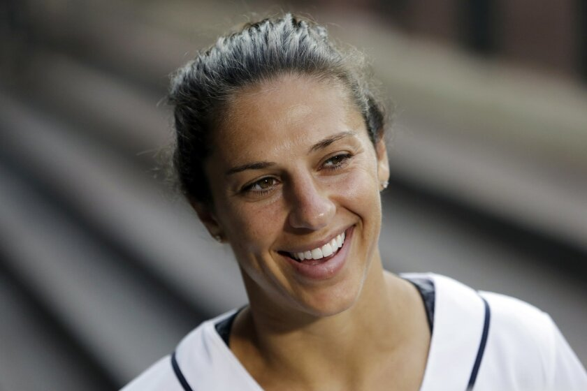 FILE - In this Tuesday, Aug. 11, 2015, file photo, U.S. national women's soccer team's Carli Lloyd smiles before throwing out the ceremonial first pitch before a baseball game between the Seattle Mariners and Baltimore Orioles, in Seattle. Lloyd is working on a memoir that Houghton Mifflin Harcourt will release in fall 2016. The publisher announced Thursday, Aug. 20, 2015, that the book, currently untitled, will cover her rise from nearly quitting soccer in 2003 and her emphasis on physical and mental strength. An edition for young readers is also planned. (AP Photo/Elaine Thompson, File)
