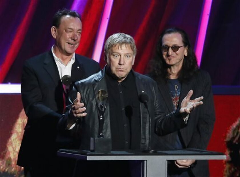 Neil Peart, left, Alex Lifeson, center, and Geddy Lee of Rush accept their band's induction into the Rock and Roll Hall of Fame during the Rock and Roll Hall of Fame Induction Ceremony at the Nokia Theatre on Thursday, April 18, 2013 in Los Angeles. Peart died on Tuesday, Jan.7, after a three-and-a-half-year battle with brain cancer. He was 67.