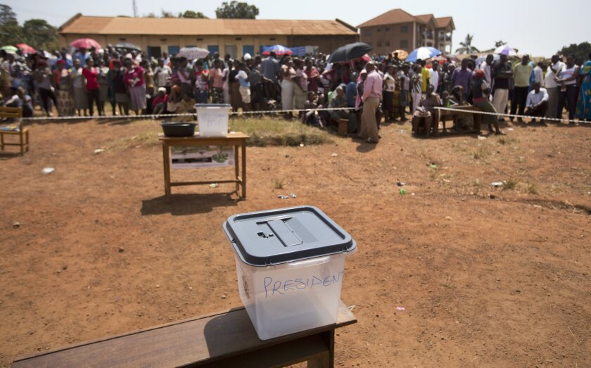 A ballot box sits empty while voters queue at a polling station where five hours after voting was due to start no voting papers had yet arrived, in the capital Kampala, Uganda, Thursday, Feb. 18, 2016. Ugandans voted Thursday in presidential elections seen as the toughest challenge yet for the coun