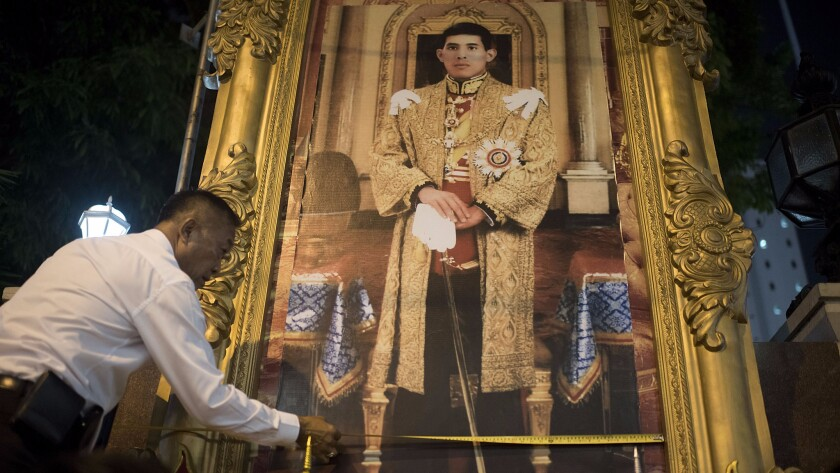 An official installs a new portrait of Crown Prince Maha Vajiralongkorn at the Thai police headuarters in Bangkok on Oct. 14, 2016.