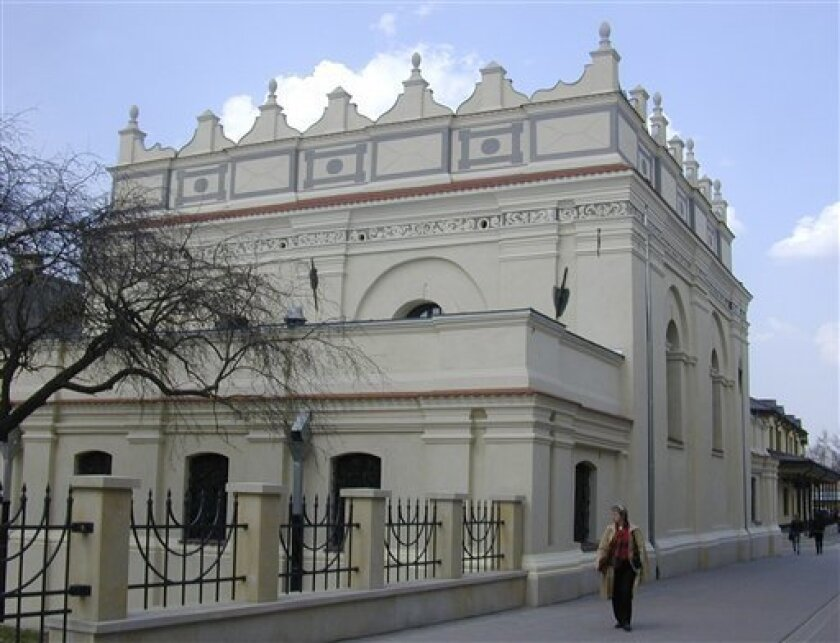 In this Thursday, March 31, 2011, photo people walk past the newly restored synagogue in Zamosc, Poland. The building is one of the most important synagogues to survive the destruction of World War II, a Renaissance gem that was looted by the Nazis and faced decades of neglect after the war, but now it has been restored and will serve as a cultural center for the town of about 65,000 in eastern Poland. It will be reintroduced to the public in an inauguration ceremony on Tuesday April 5, 2011. (AP Photo/Vanessa Gera)