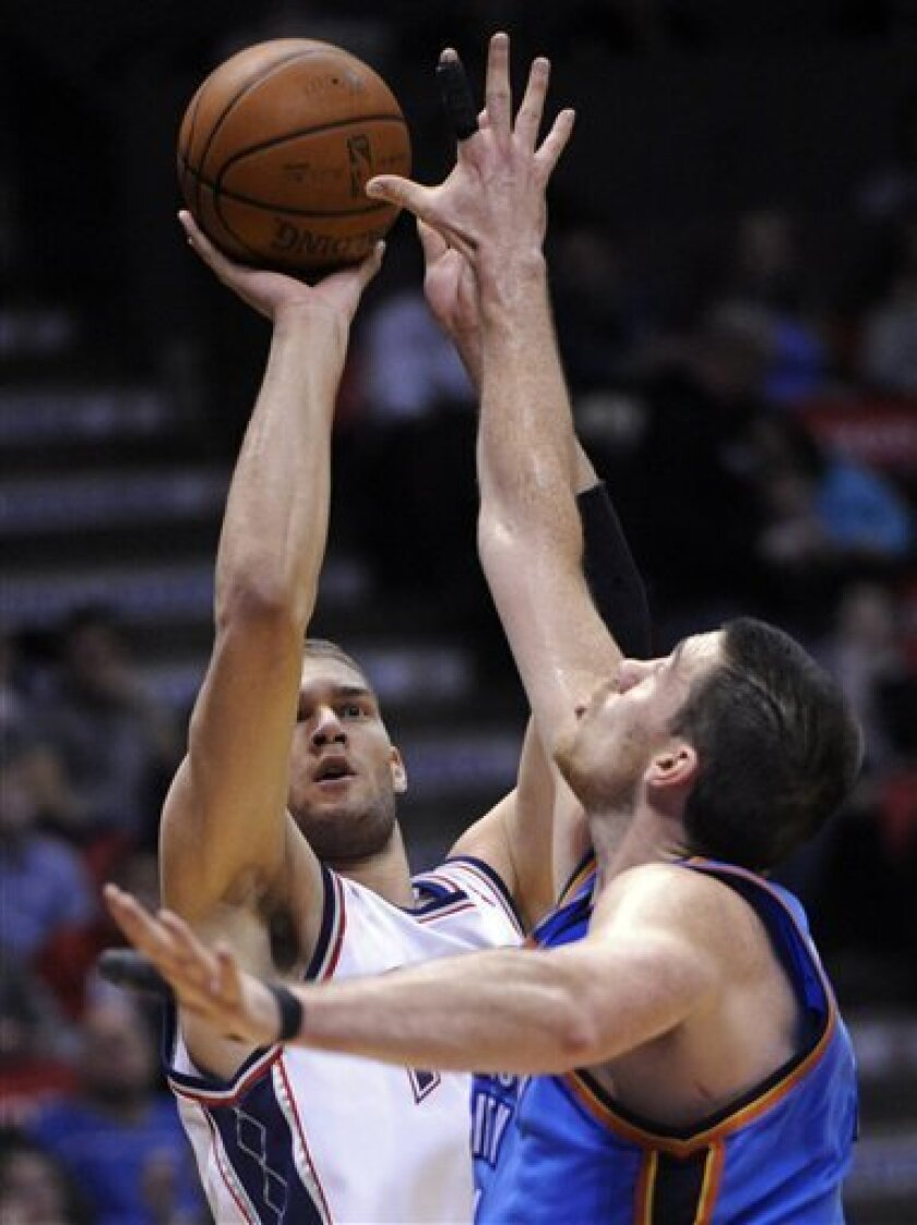 New Jersey Nets center Brook Lopez, ledt, shoots over Oklahoma City Thunder center Nick Collison during the second quarter of an NBA basketball game Monday, Jan. 12, 2009 in East Rutherford, N.J. (AP Photo/Bill Kostroun)
