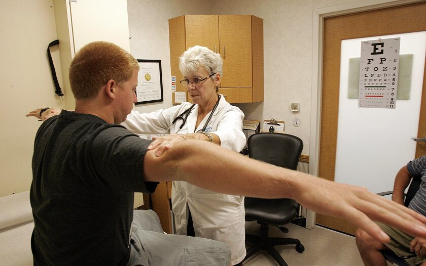 """This CVS """"minute clinic"""" on Fletcher Parkway is one of several that have cropped up, most staffed with nurse practitioners like Dawn Clapham, right, who checks the strength of Matt Cass, who came in for a sports physical."""