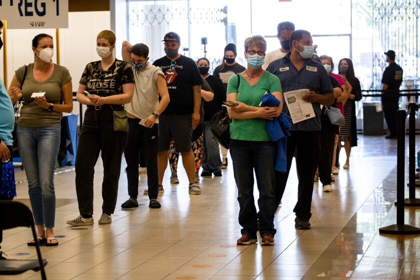 People wait in line to get COVID-19 vaccines at a converted former Sears building at Chula Vista Center in March.