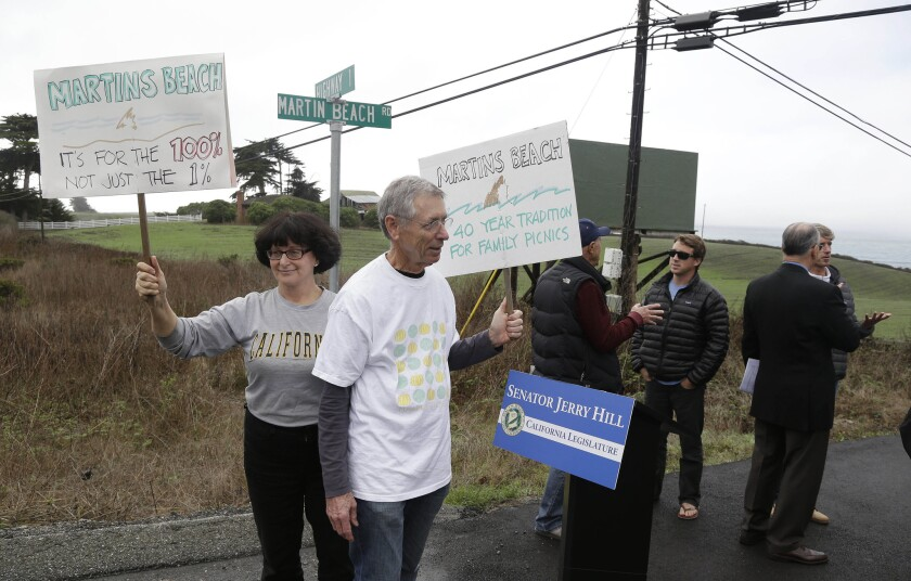 Protesters in February hold up signs in support of a beach access bill near Martin's Beach in Half Moon Bay.