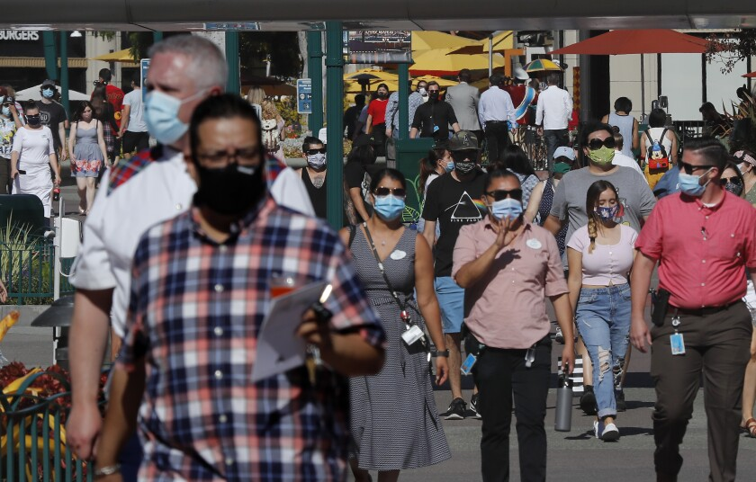 Scores of visitors wearing masks walk through Downtown Disney in Anaheim for its reopening