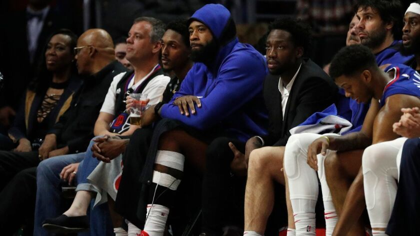 Clippers center DeAndre Jordan, middle, sits on the bench with a left ankle sprain for a game against the Sacramento Kings on Jan. 13 at Staples Center.