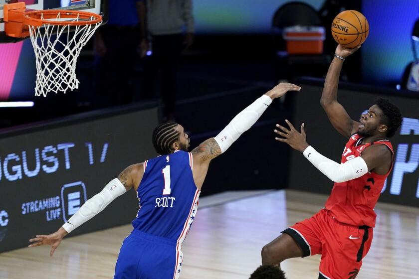 Toronto Raptors' Terence Davis, right, shoots against Philadelphia 76ers' Mike Scott during the second half of an NBA basketball game Wednesday, Aug. 12, 2020 in Lake Buena Vista, Fla. (AP Photo/Ashley Landis, Pool)