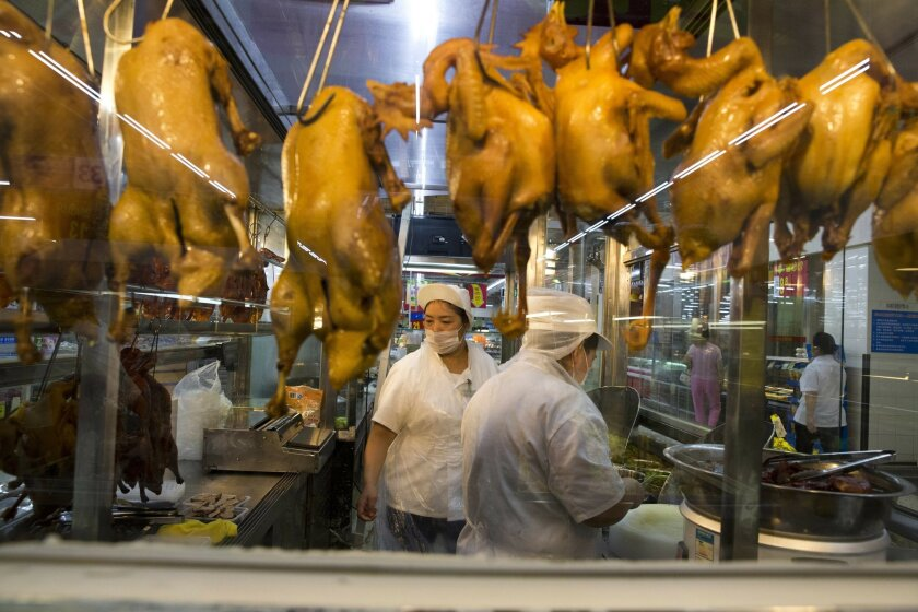 In this Wednesday, Nov. 11, 2015, photo, a worker prepares cooked ducks for sale at a Wal-Mart in Shenzhen, in southern China's Guangdong province. If Arkansas-based Wal-Mart wants to win over foreign consumers, it has to shed some of its American ways, and cater to very different customs and conventions. China is the ultimate prize. (AP Photo/Ng Han Guan)