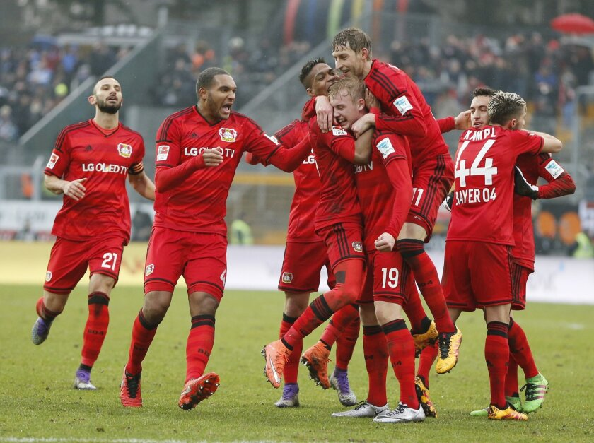 Leverkusen's players celebrate their side's second goal during a German Bundesliga soccer match between SV Darmstadt 98 and Bayer Leverkusen in Darmstadt, Germany, Saturday, Feb. 13, 2016. (AP Photo/Michael Probst)