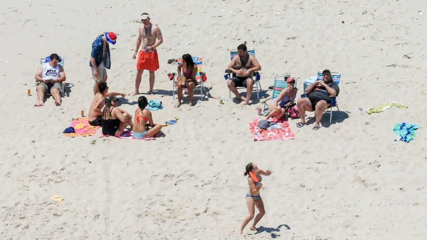 New Jersey Gov. Chris Christie, right, uses the beach with his family and friends at the governor's summer house at Island Beach State Park while the beach was closed to the public because of a government shutdown.