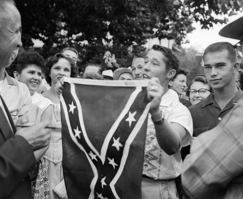 FILE - In this Sept. 3, 1957 file photo, Paul Davis Taylor holds a Confederate flag in front of Little Rock Central High School in Little Rock, Ark. Taylor was among some 500 people who gathered across the street from the school, which had been scheduled to integrate. More than 50 years after South