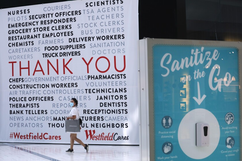A person walks in front of a wall at a Westfield mall with messages thanking workers