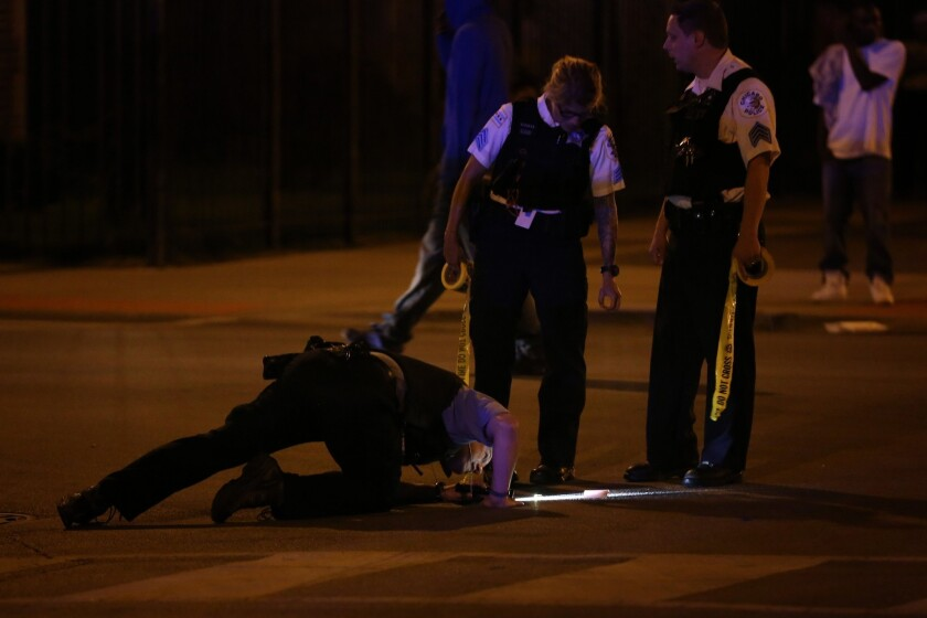 Chicago police investigate the scene of a shooting earlier this summer.