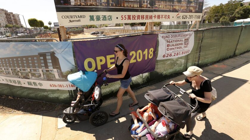 Emily Morales, left, and Veronika Luu pass the construction site for the Courtyard by Marriott in Mo