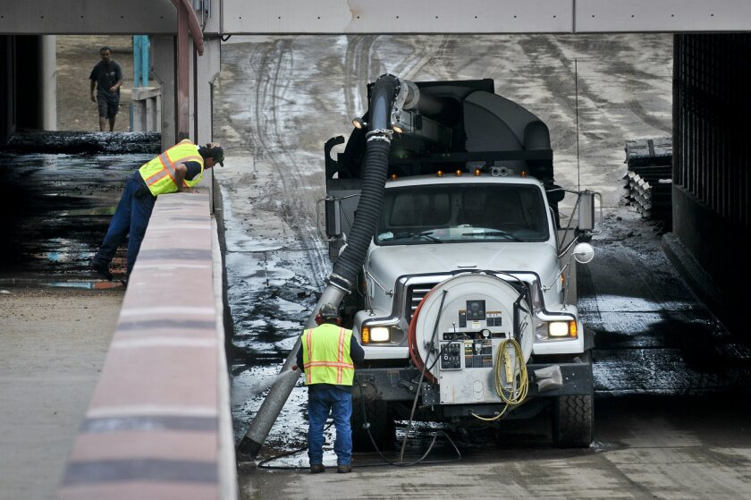 Storm crews work on cleaning up Central Avenu under the First Street bridge, Saturday, Aug. 2, 2014, after a flash flood surged under the bridge Friday in Albuquerque, N.M. A deluge of rain flooded downtown Albuquerque and led to stranded residents needing rescue, authorities said Saturday. (AP Photo/The Albuquerque Journal, Marla Brose)