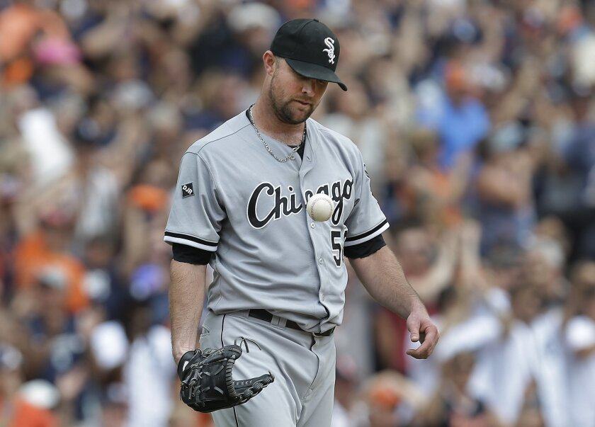 Chicago White Sox pitcher John Danks tosses a ball after allowing back to back solo home runs to Detroit Tigers' Torii Hunter and J.D. Martinez in the third inning of a baseball game in Detroit,  Thursday, July 31, 2014. (AP Photo/Paul Sancya)