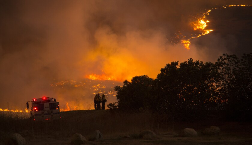 Firefighters gather to observe the Sherpa fire on Thursday as it approaches Highway 101 near Refugio Road in Santa Barbara County.