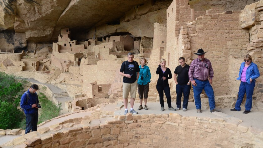 Tourists assess Cliff Palace in Mesa Verde National Park, Colo.