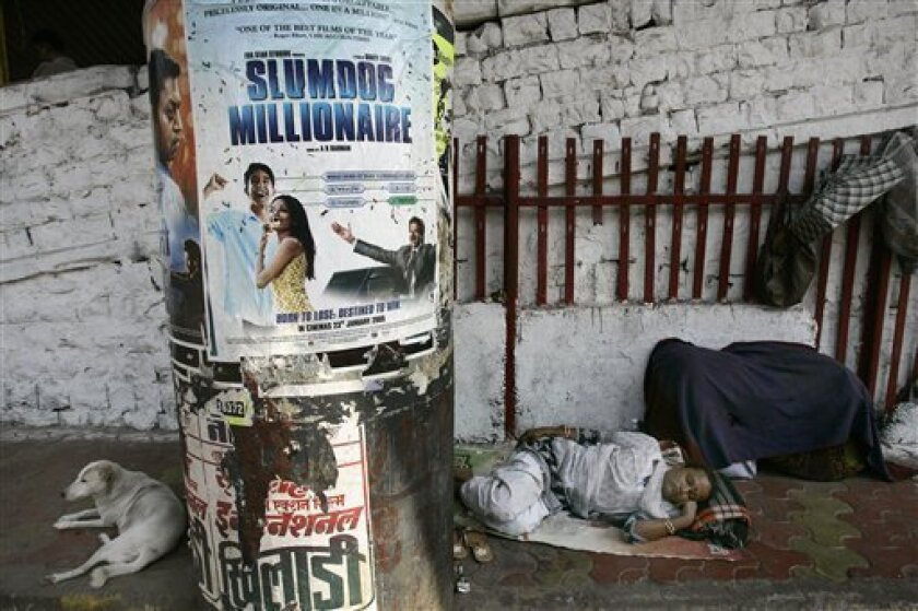 """A man sleeps near a poster of """"Slumdog Millionaire,"""" posted on a pillar in Mumbai, India, Tuesday, Jan. 13, 2009. India's movie-mad millions have not yet seen """"Slumdog Millionaire,"""" but this Mumbai-based fairy tale, which opens here next week, is already the toast of Bollywood. On Sunday, """"Slumdog?"""