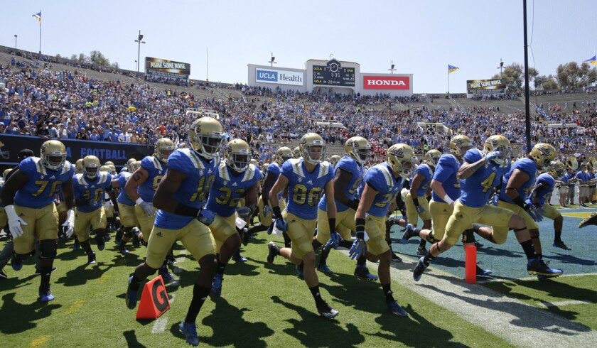 UCLA players run onto the field before agame at the Rose Bowl.