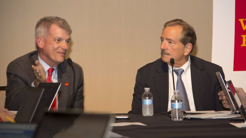 Wells Fargo CEO Tim Sloan, left, and Chairman Stephen Sanger speak with reporters after the company's annual meeting in April.