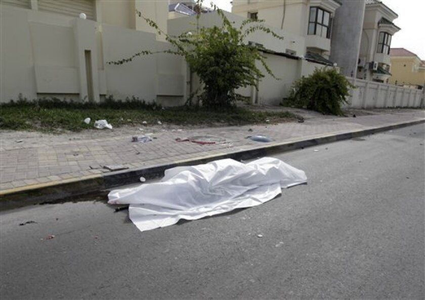 The body of a person killed during clashes between demonstrators and police lies in the street in Manama, Bahrain on Thursday, Feb. 17, 2011. Army patrols and tanks locked down the capital of this tiny Gulf kingdom after riot police swinging clubs and firing tear gas smashed into demonstrators, man