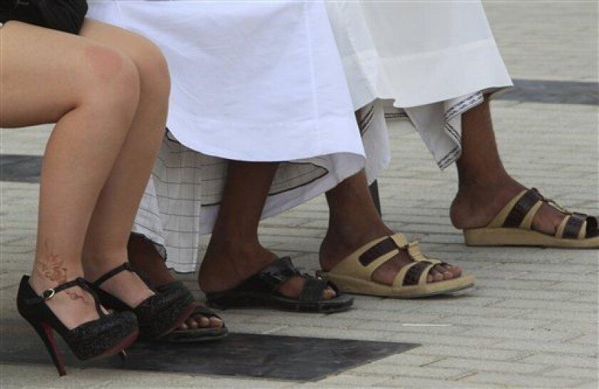 a women in western dress, left, sits next to Arab men during the Dubai World Cup horse race, Saturday, March 31, 2012, in Dubai, United Arab Emirates. (AP Photo/Kamran Jebreili)