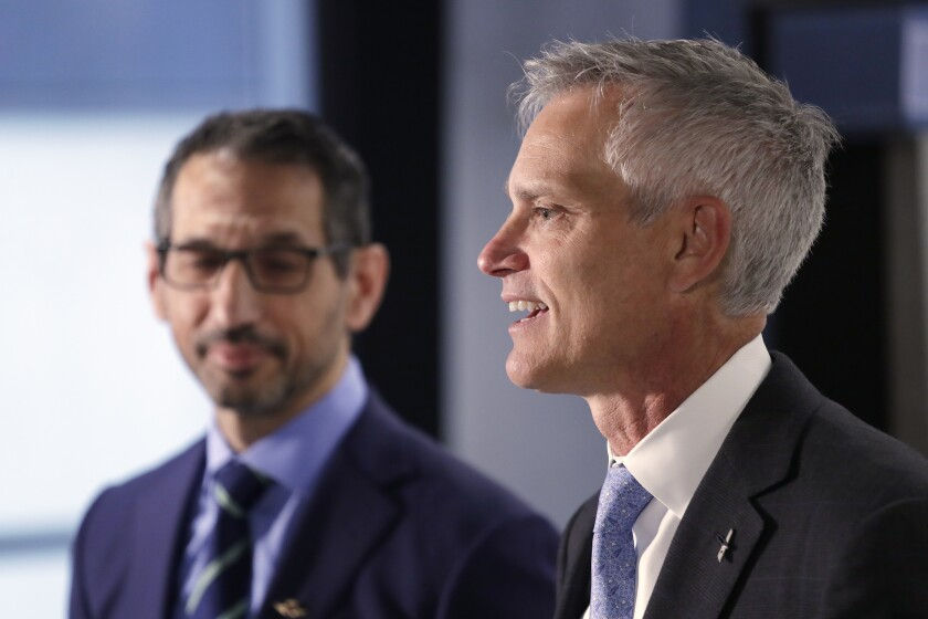 Alaska Airlines President Ben Minicucci, left, looks on as American Airlines President Robert Isom addresses a news conference about the companies new partnership Thursday, Feb. 13, 2020, in Seattle. The airlines say they will cooperate more closely on West Coast service, including new American flights from Seattle to India's technology hub in Bangalore. The airlines already share revenue by selling seats on each other's flights, but they had planned to reduce that partnership next month. Instead, they announced that they will expand revenue-sharing to cover international flights in Seattle and Los Angeles. (AP Photo/Elaine Thompson)