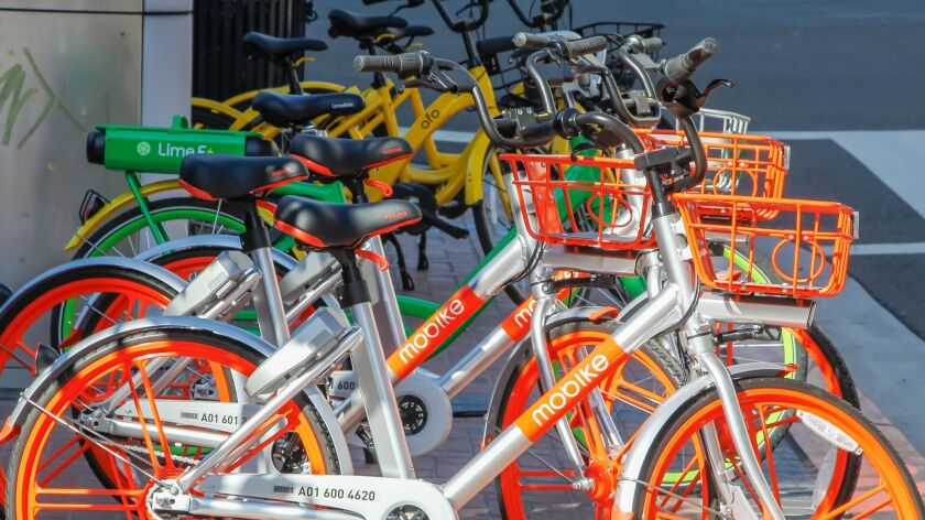 Some of the multi-colored Mobikes, LimeBikes, and Ofo bikes parked along Broadway in downtown San Diego.