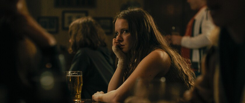 """Morfydd Clark sits at a bar with a pint of beer in front of her in """"Saint Maud."""""""