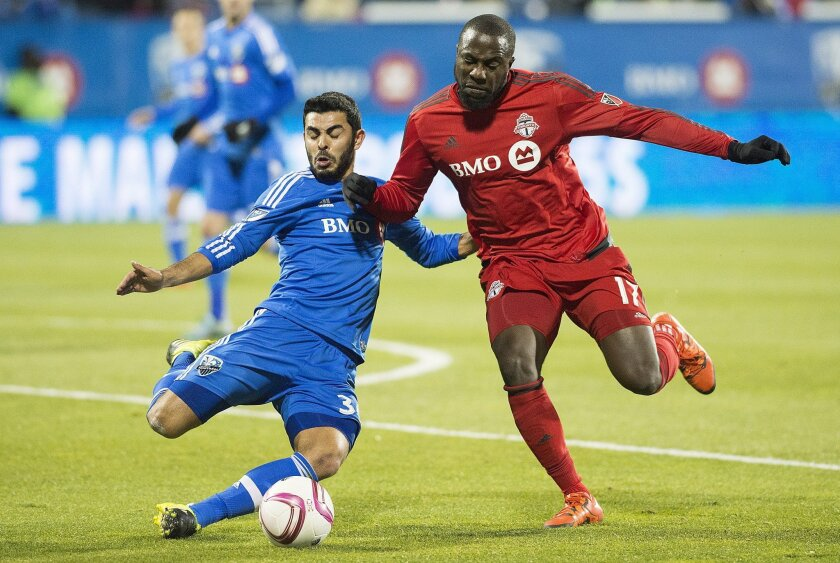 FILE - In this Oct. 29, 2015 file photo, Montreal Impact's Victor Cabrera, left, is challenged by Toronto FC's Jozy Altidore during second-half MLS soccer playoff game in Montreal. Altidore craves a major role in World Cup qualifying in March 2016 and the Copa America in June, so he showed up to th