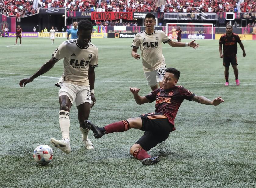 Atlanta United midfielder Ezequiel Barco gets off a shot on goal past Los Angeles FC defender Mamadou Fall