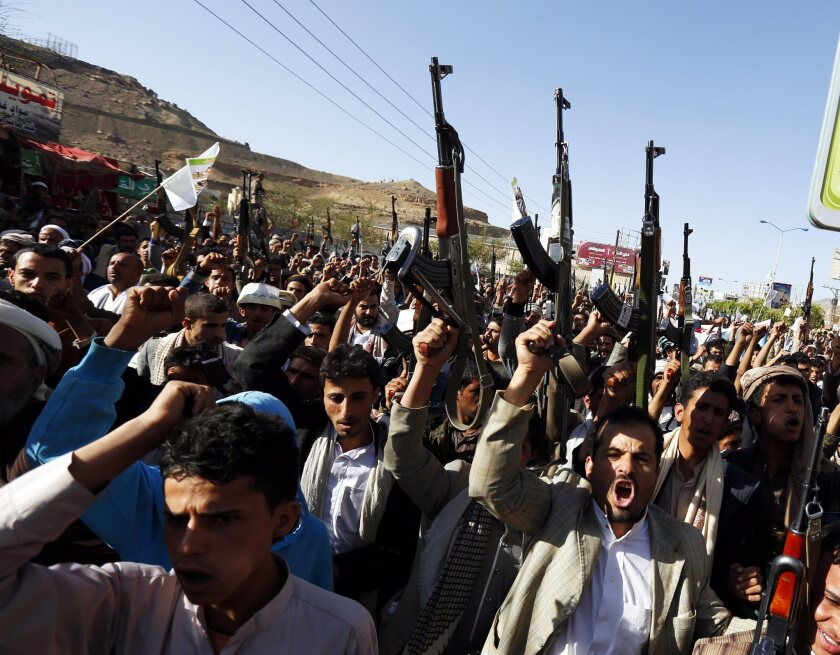 Houthi supporters rally in the Yemeni capital, Saana, some with rifles pointed in the air.
