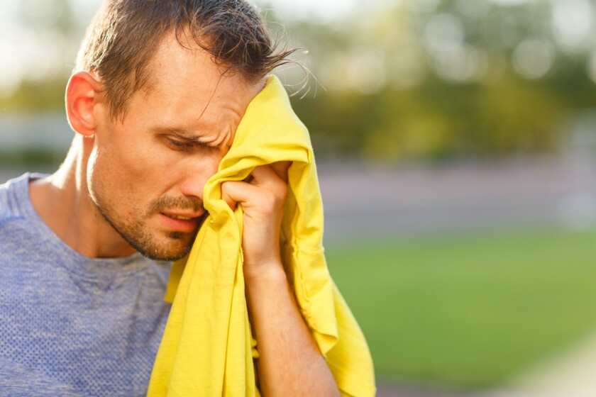 Athletic man wipes his face with yellow towel