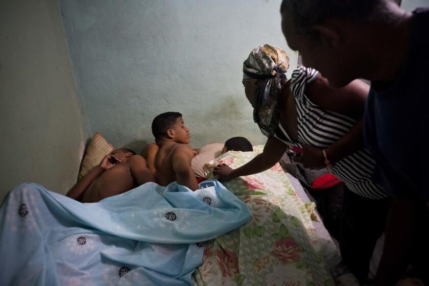 La pareja formada por Leandro Heredia Marrero (d) y su esposa Leticia despiertan a tres jóvenes luchadores que se alojan en su casa para un torneo amateur organizado por vecinos del vecindario de Chicharrones, en Santiago, Cuba.