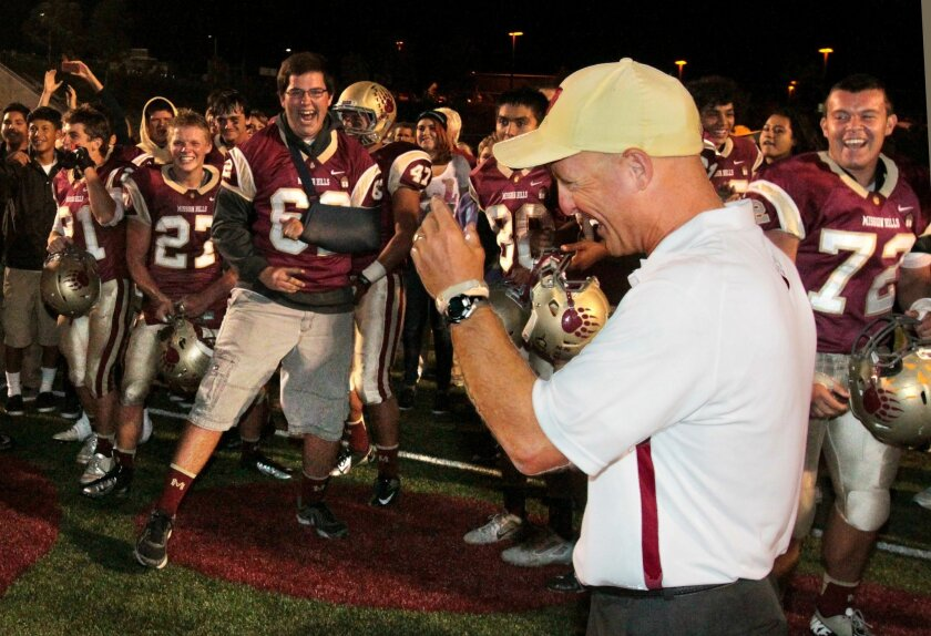 Mission Hills' coach Chris Hauser celebrates with his players after their 30 to 6 victory.