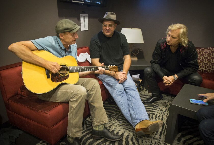 Backstage at the Novo, James Taylor, left, Vince Gill and Joe Walsh share stories about the impact music-making played in their lives growing up.