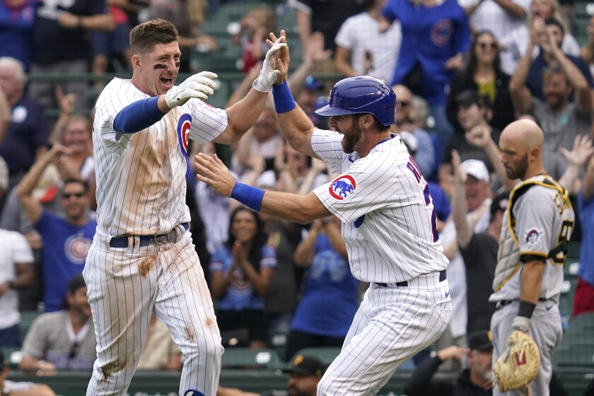 Chicago Cubs' Frank Schwindel, left, celebrates with Alfonso Rivas, center, after hitting the game-winning single as Pittsburgh Pirates catcher Jacob Stallings looks down in the ninth inning of a baseball game in Chicago, Saturday, Sept. 4, 2021. The Cubs won 7-6. (AP Photo/Nam Y. Huh)