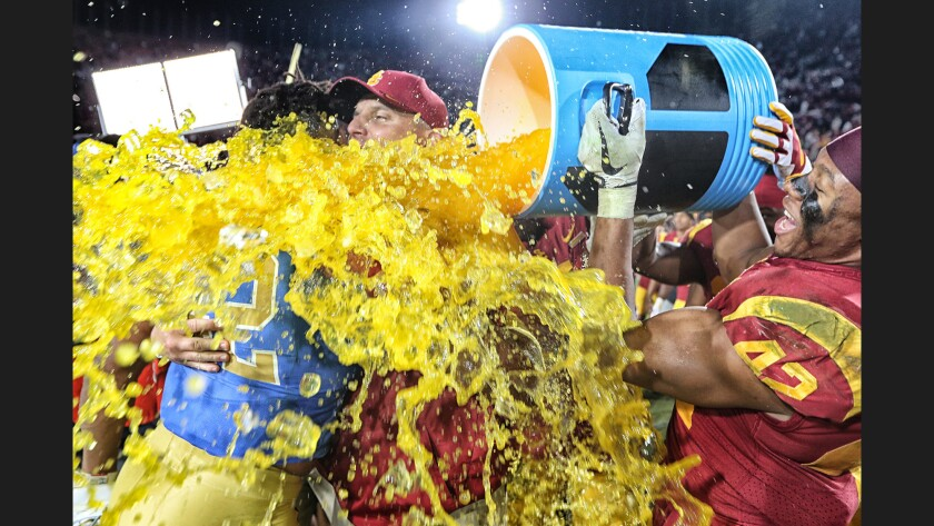 USC linebacker Uchenna Nowosu hits coach Clay Helton with a Gatorade bath following a 28-23 win over UCLA at the Coliseum.