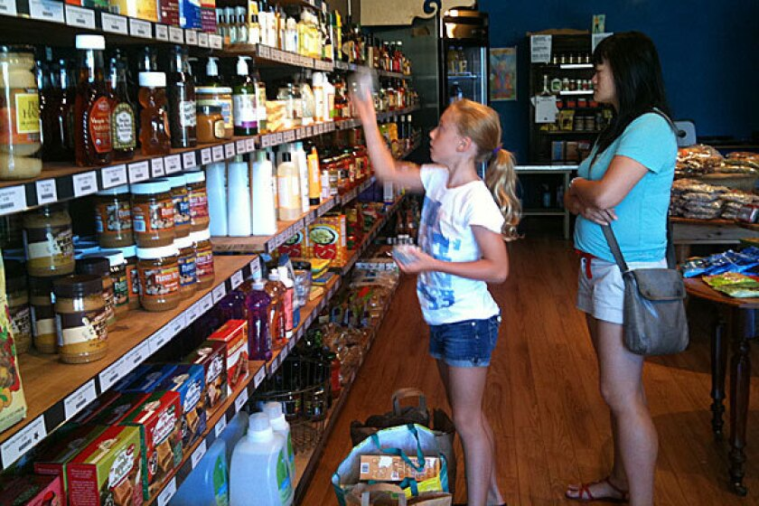Here, Mike Hallatt's 9-year-old daughter, Josie, helps stock shelves. He says he's a huge fan of Trader Joe's, its products, and the way it caters to consumers' wallets.